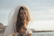 Bride riding piggyback on groom on beach against sunset - CUF30097
