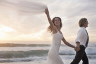 Bride and groom running on beach against sunset - CUF30100