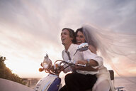 Bride and groom riding motorcycle on beach against sunset - CUF30103