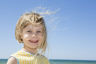 Portrait of girl with blond flyaway hair on beach - CUF30106