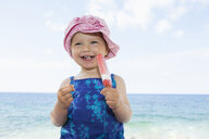 Female toddler wearing sunhat eating ice lolly on beach - CUF30109