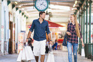 Young couple carrying shopping bags in arcade - CUF30142