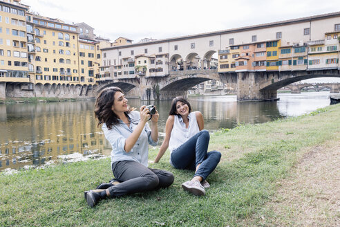 Lesbian couple sitting on arno river bank in front of Ponte Vecchio holding digital camera smiling, Florence, Tuscany, Italy - CUF30169