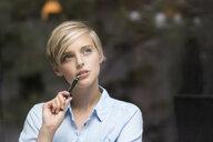 Young woman gazing through window - CUF30193