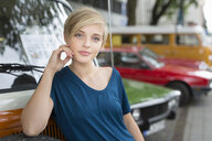 Portrait of young woman leaning against campervan - CUF30196