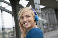 Happy young woman wearing headphones on bridge looking over her shoulder - CUF30202