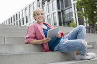 Young woman using digital tablet on city stairway - CUF30205