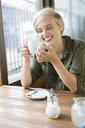 Young woman drinking coffee at cafe table - CUF30208