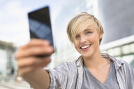Young woman taking smartphone selfie in city - CUF30217