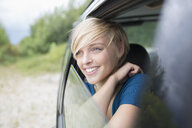 Young woman looking out of open car window - CUF30223