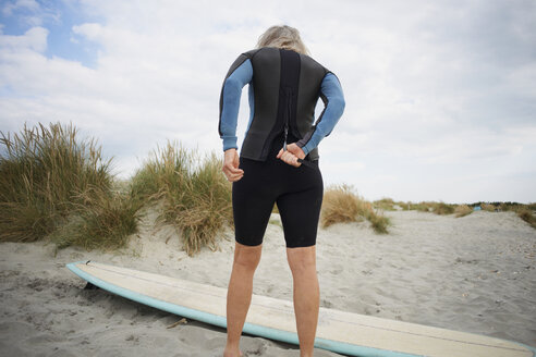 Senior woman putting on wetsuit, rear view - CUF30250