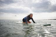 Senior woman on surfboard in sea, paddleboarding - CUF30253