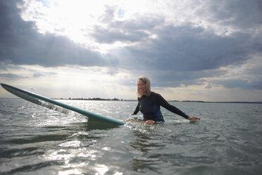 Portrait of senior woman sitting on surfboard in sea, smiling - CUF30256