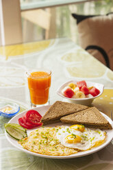 High angle view of fried eggs and omelette breakfast with wholemeal bread, fruit salad and orange juice - CUF30415