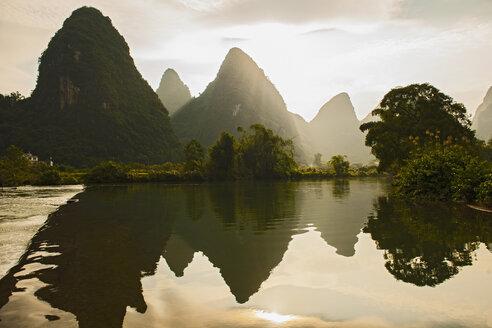 Mirror image of mountains in Li river at sunset, Yangshuo, Guangxi Zhuang, China - CUF30433