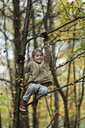 Girl hanging on to tree branch in autumn forest - CUF30519