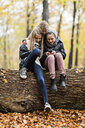 Girls using smartphone on tree trunk in autumn forest - CUF30525