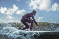 Male surfer riding wave - CUF30663