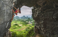 Female climber at treasure cave in Yangshuo, Guangxi Zhuang, China - CUF30675