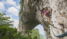 Female climber climbing on Moon Hill limestone arch in Yangshuo, Guangxi Zhuang, China - CUF30678