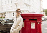 Stylish young man leaning against red post box, London, England, UK - CUF30777