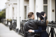 Rear view of romantic young couple strolling on street, London, England, UK - CUF30786