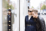 Young couple looking in shop window, London, England, UK - CUF30789