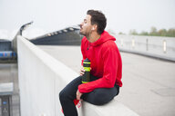 Young male runner sitting on rooftop edge with water bottle - CUF30798