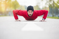Surface level portrait of young man doing push up training in city park - CUF30804
