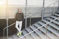 Young male runner leaning against sport arena stairway - CUF30807