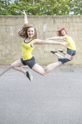 Young women jumping in front of concrete wall - CUF30876