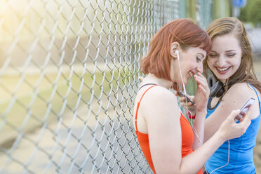 Young women using smartphone beside fence, London, UK - CUF30882