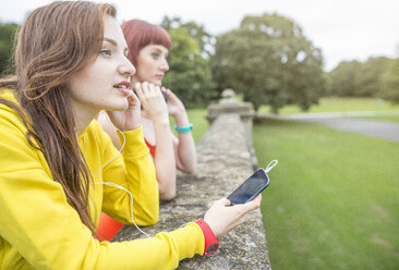 Young woman with smartphone leaning against stone wall - CUF30885