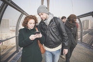 Young adult friends on footbridge reading smartphone text - CUF31158