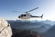 Helicopter transporting BASE jumpers to summit, Dolomites, Italy - CUF31194