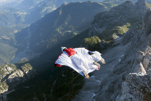 Two male BASE jumpers wingsuit flying from mountain, Dolomites, Italy - CUF31197