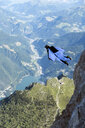 Male BASE jumper wingsuit flying over valley, Dolomites, Italy - CUF31200