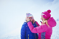 Mother helping daughter with sunglasses, Chamonix, France - CUF31269