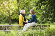 Senior woman and daughter holding hands on park bench - CUF31329