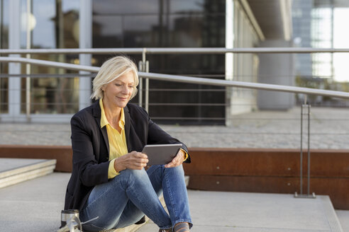 Smiling senior businesswoman sitting with tablet in the city - FMKF05138