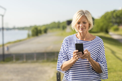 Smiling senior woman using cell phone at riverbank - FMKF05147