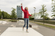 Carefree senior woman wearing red hoodie outdoors - FMKF05153