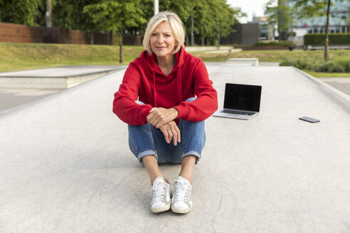 Senior woman wearing red hoodie sitting outdoors with laptop - FMKF05156