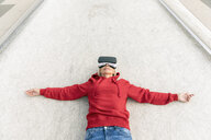 Senior woman lying on the ground wearing VR glasses - FMKF05159