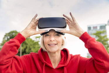 Portrait of smiling senior woman wearing VR glasses - FMKF05162