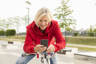 Smiling senior woman with city bike using cell phone - FMKF05165