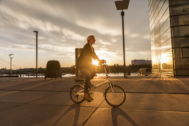 Senior woman riding city bike at the riverside at sunset - FMKF05174