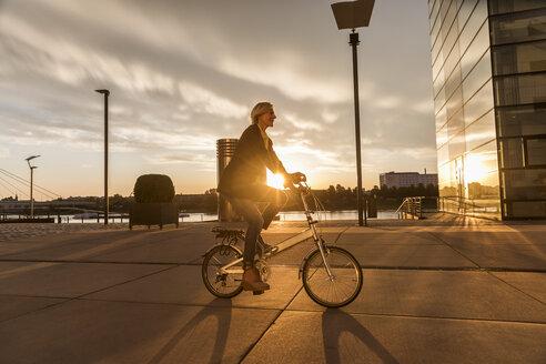 Senior woman riding city bike at the riverside at sunset - FMKF05174