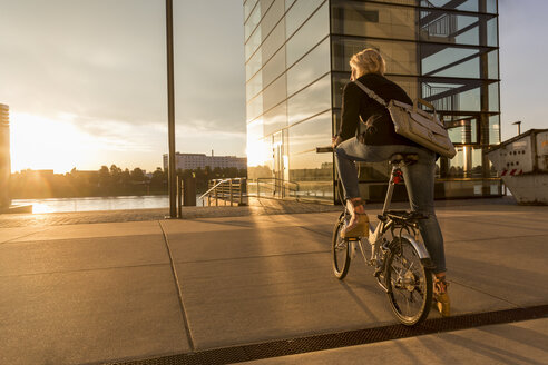 Senior woman with city bike at the riverside at sunset - FMKF05177