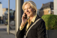 Smiling senior businesswoman on cell phone outdoors - FMKF05180